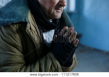 Old homeless man is praying for help.