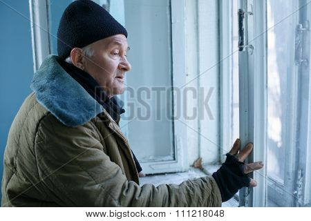 Homeless man is looking out of the window.
