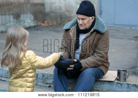 Little girl gives money to the beggar.