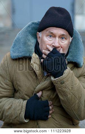 Homeless senior-aged man looks startled an alarmed.