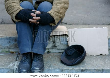 Asking for help. Depressed old beggar is sitting outside and waiting to get some help. poster