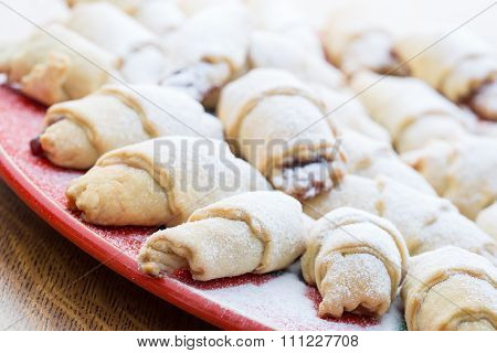 Freshly baked cookies on red plate with sugar powder, soft focus.