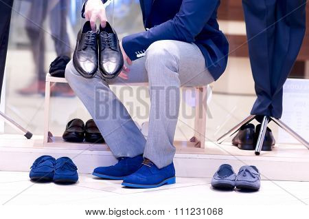 Attractive Young  Man Chooses A Shoes  At A Shop.