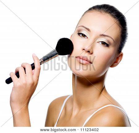 Woman Applying Powder On Cheek With Brush
