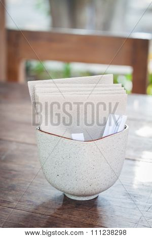 Tissue Paper In Ceramic Cup On Wooden Table