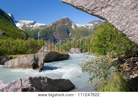 Norway. A Heavy Water Flow From The Thawing Glacier Briksdayl In Mountains In The Summer Afternoon A