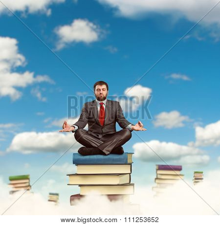 Businessman meditates sitting on the heap of the books in the clouds