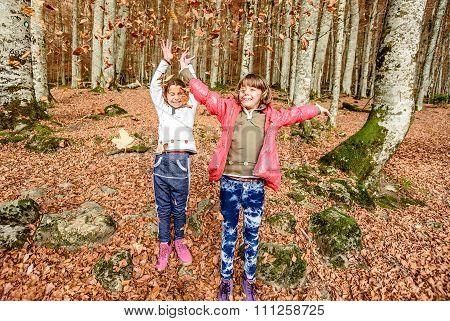 Little Girls  Having Fun With Laves In Autumn In Biogradska Gora National Park, Montenegro