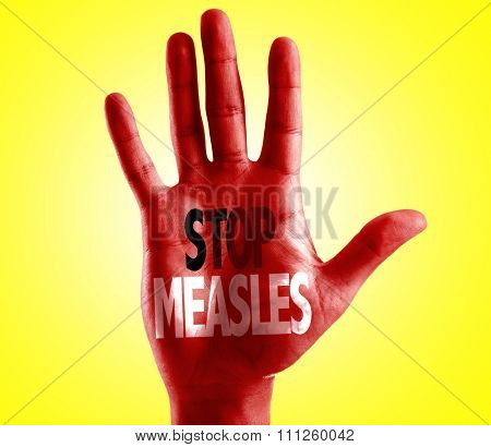 Stop Measles written on hand with yellow background