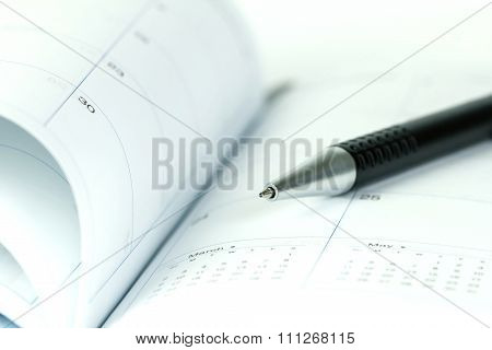 Selective Focus Of Ball Pen On Opened Lined Diary Book With Calendar Page