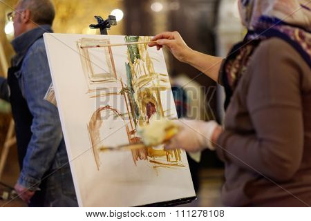 MOSCOW, RUSSIA - NOVEMBER 27, 2015: Professional painters help talented children from large families to draw their guardian angel during the annual action