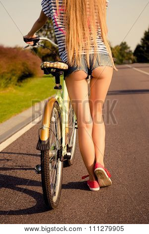 Shapely Girl With Sexy Buttoks And Mini Shorts Walking With Bicycle