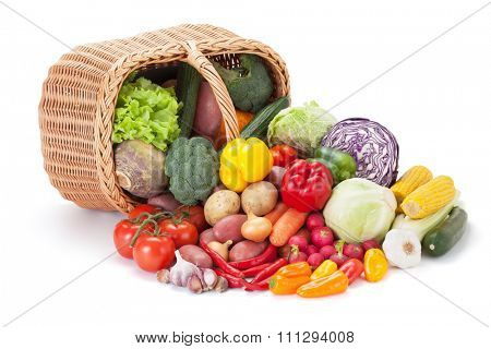 Fresh vegetables next to the overturned basket, isolated on the white background.