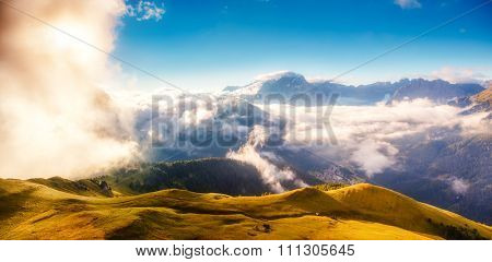 View of the foggy Val di Fassa valley. National Park. Dolomites (Dolomiti), pass Sella. South Tyrol. Location famous resort Canazei, Campitello, Mazzin. Italy, Europe. Dramatic scene. Beauty world.
