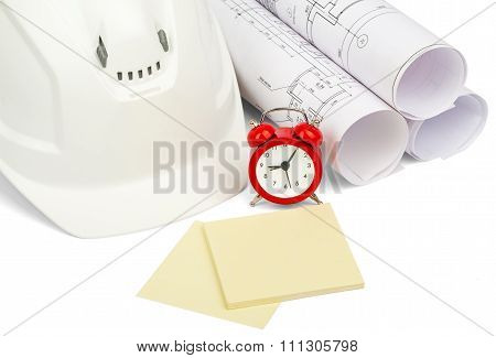 Blueprint rols and helmet with pavement tile