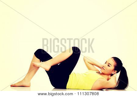 Woman exercising and doing a crunch to work her abs.
