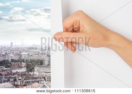 Hand turning page to city