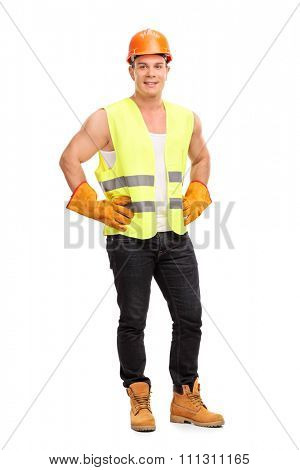 Full length portrait of a young construction worker with an orange helmet and a green reflective vest isolated on white background