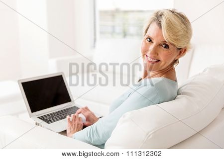 cheerful mid age woman with laptop computer at home