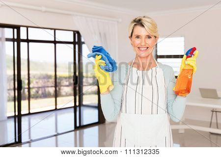 portrait of happy middle aged woman holding cleaning products at home