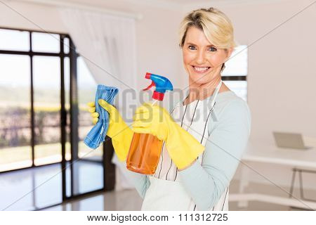 happy senior woman holding cleaning tools at home