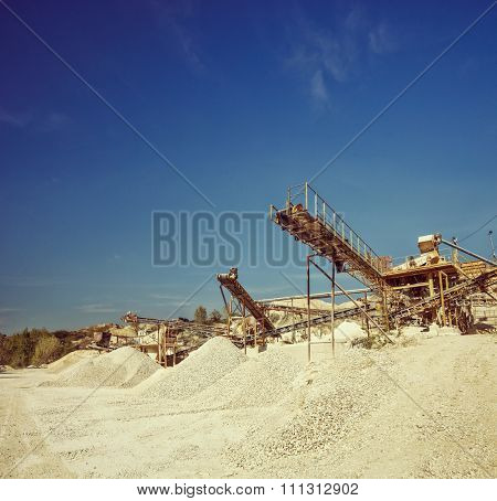 Conveyor belts and machinery at a gravel pit shot on a clear sunny day shot with tilt and shift lens