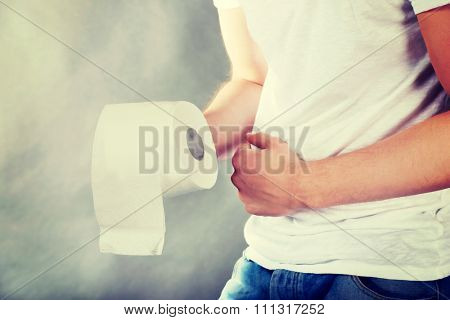 Young man with stomach issues holding toilet paper.