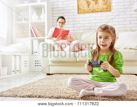 family relax. mother reading a book, child playing video games.