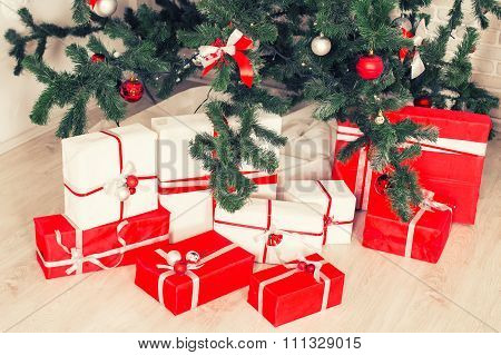 New Year and Christmas gifts near a Christmas tree. Red, white and green colors. Gifts with ribbon,