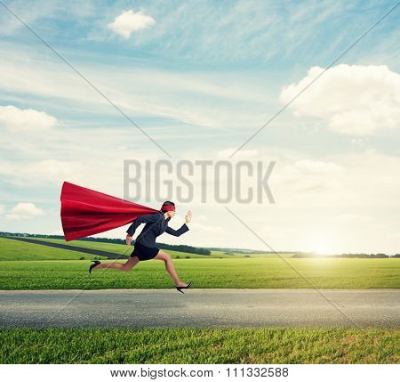 concentrated superwoman in formal wear and red cloak with mask fast running on the road at outdoor