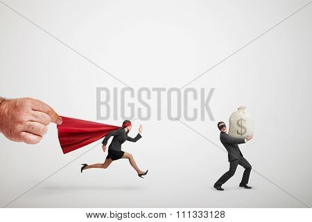 big mans hand holding the red cloak of superwoman that chasing the thief with big bag of money over light grey background