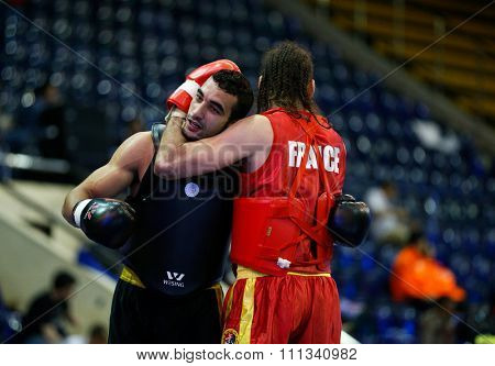 JAKARTA, INDONESIA - NOVEMBER 17, 2015: Yoan Benedra of France (red) embraces Ayman Mohamed of Egypt (black) after their fight in the men's 70kg Sanda event at the 13th World Wushu Championship 2015.