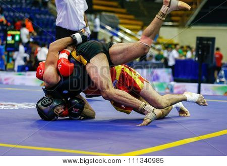 JAKARTA, INDONESIA - NOVEMBER 17, 2015: Yoan Benedra of France (red) fights Ayman Mohamed of Egypt (black) in the men's 70kg Sanda event at the 13th World Wushu Championship 2015.
