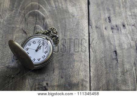 Pocket Watch And Chain Against Aged Wood