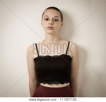 Shaven Bald Teenage Girl With Black Top And Bare Shoulders