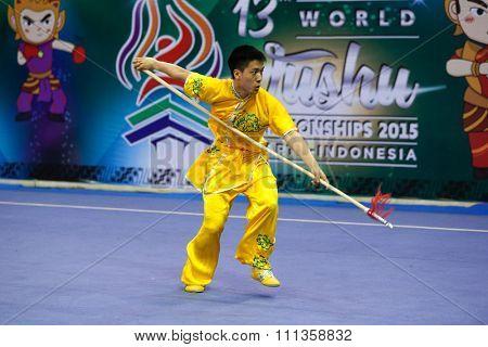 JAKARTA, INDONESIA - NOVEMBER 17, 2015: Reagan Tan of Australia performs the movements in the men's Qiangshu event at the 13th World Wushu Championship 2015 at the Istora Senayan Stadium.