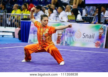 JAKARTA, INDONESIA - NOVEMBER 17, 2015: Eyin Poon of Malaysia performs the movements in the women's Compulsory Changquan event at the 13th World Wushu Championship 2015 at the Istora Senayan Stadium.