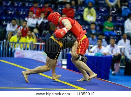 JAKARTA, INDONESIA - NOVEMBER 17, 2015: Kazbek Mamaev of Russia (red) fights Van Cao Hoang of Vietnam (black) in the men's 65kg Sanda event at the 13th World Wushu Championship 2015.