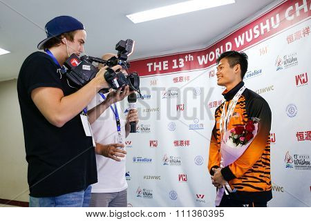 JAKARTA, INDONESIA - NOVEMBER 16, 2015: Wushu TV crew interviews Jack Chang Loh of Malaysia after he won gold in the men's Compulsory Taijiquan event at the 13th World Wushu Championship 2015.