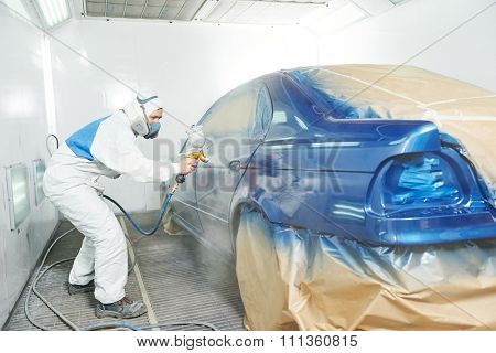 automobile repairman painter in protective workwear and respirator painting car body bumper in paint chamber poster
