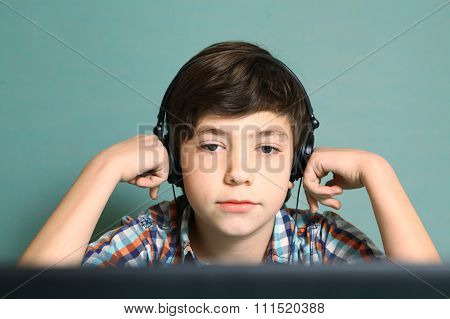 preteen handsome boy with headphones listen to popular mp3 music on computer close up expression portrait isolated on blue
