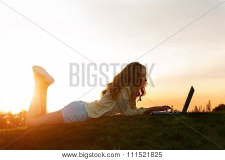 Girl with computer in nature.