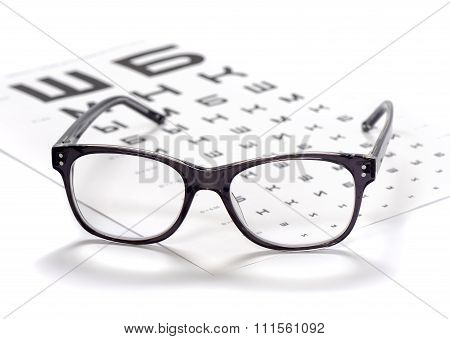 Reading eyeglasses and eye chart close-up on a light background