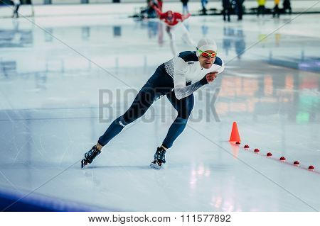 man athlete speedskater during race sprint distance along path of ice Palace