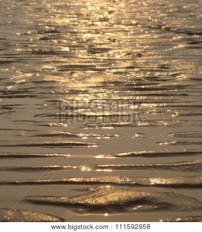 Reflection of a sunset on sandy water's edge