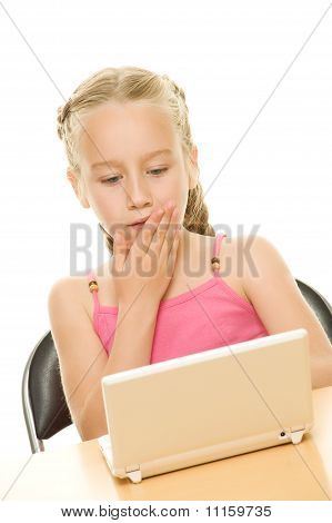 Surprised little girl sitting with a laptop