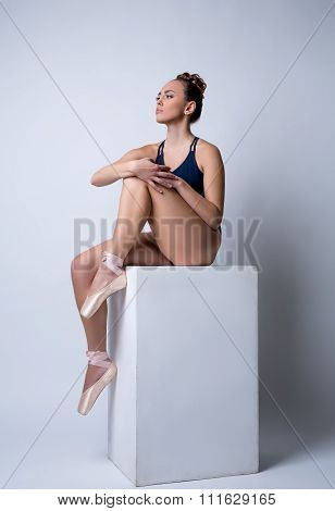 Beddable ballerina sitting on cube in studio