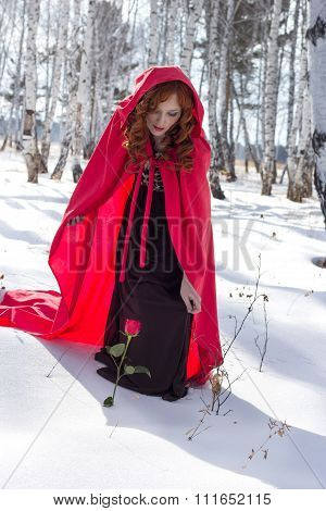The girl in a red raincoat found a rose in the snow
