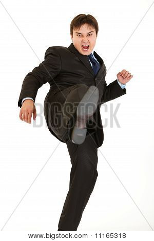 Very angry young businessman hard kicking isolated on white