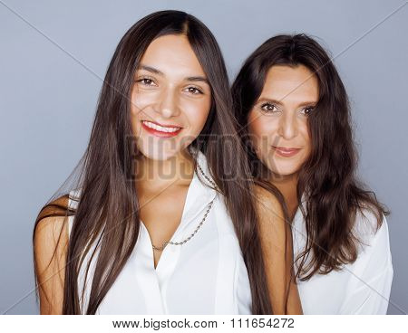cute pretty teen daughter with mature mother hugging, fashion style brunette makeup close up tann mu